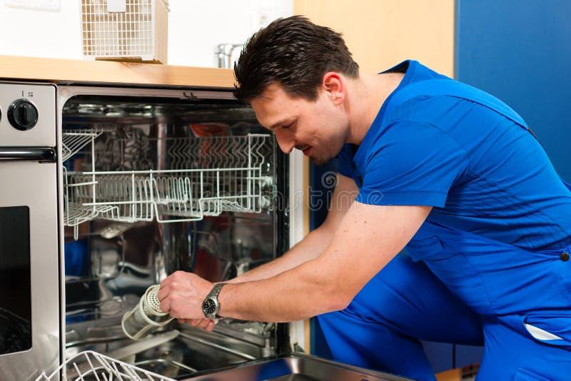 Technicien réparant le lave-vaisselle photographie stock libre de droits