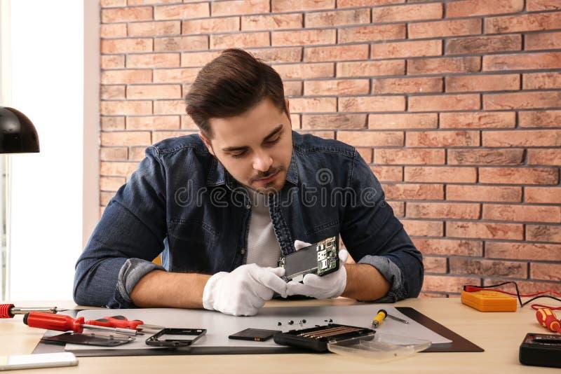 Technicien réparant le smartphone cassé dans l'atelier image stock