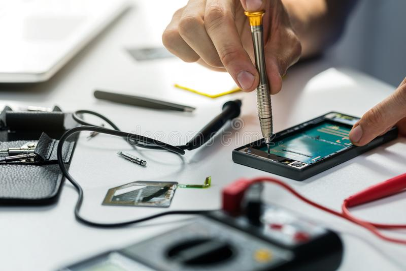 Technicien réparant le téléphone cassé photographie stock