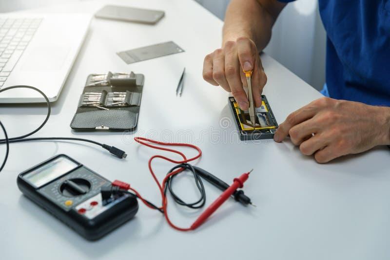 Technicien réparant le téléphone défectueux images libres de droits