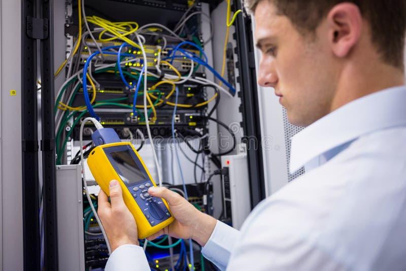 Technicien sérieux employant l'analyseur numérique de câble sur le serveur photographie stock libre de droits