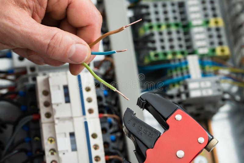 Technicien tenant les câbles et l'outil de travail photographie stock