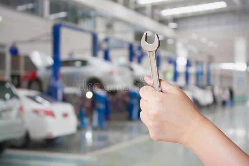 Technicien tenant une clé avec le backg de centre de service des réparations de voiture photo libre de droits