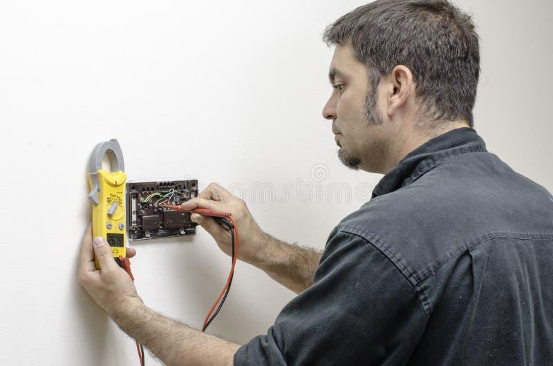 Technicien travaillant à un thermostat images libres de droits