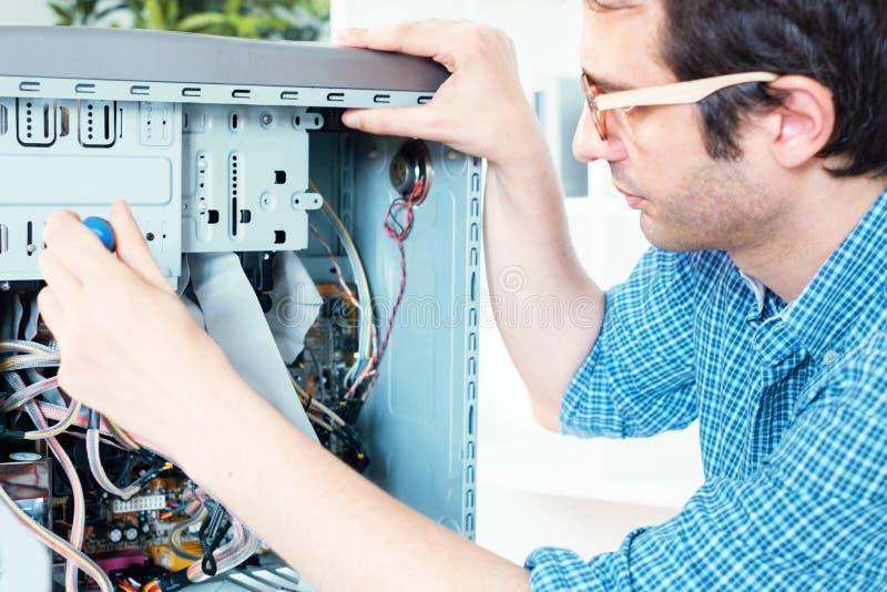 Technicien travaillant sur l'ordinateur cassé dans son bureau photo libre de droits