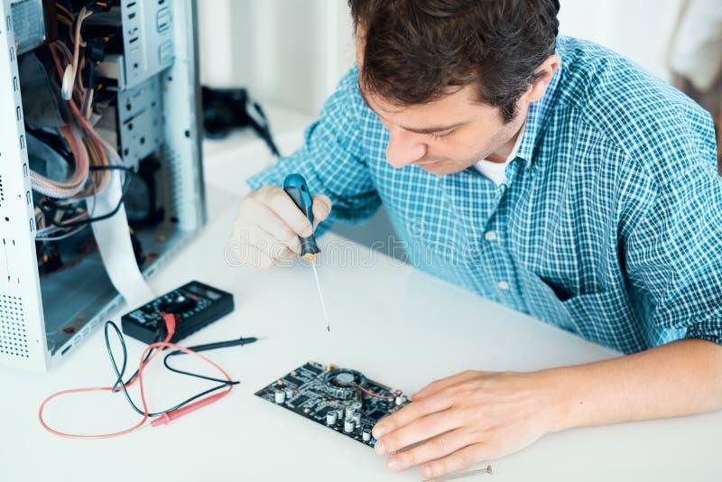 Technicien travaillant sur l'ordinateur cassé dans son bureau images libres de droits