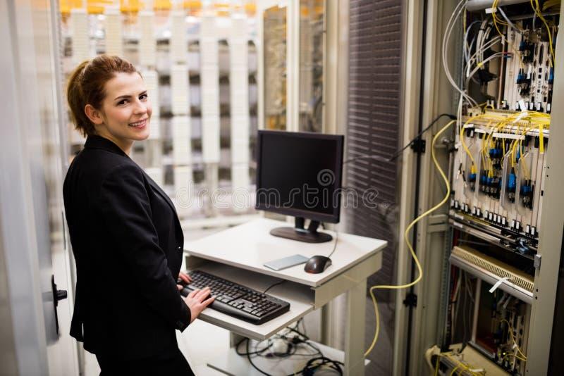 Technicien travaillant sur l'ordinateur tout en analysant le serveur image stock