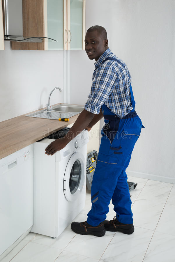 Technicien With Washing Machine dans la cuisine image stock