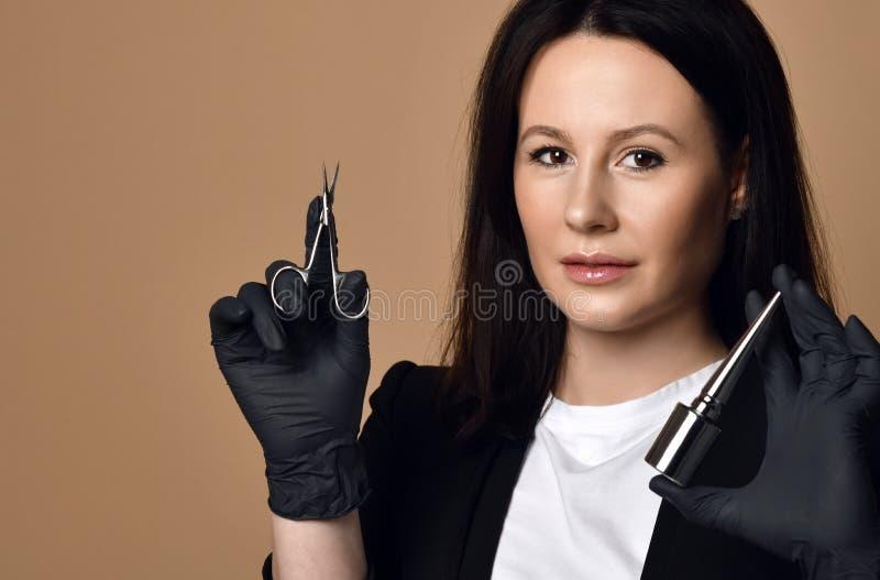 Techniciens de clou dans les gants noirs avec les ciseaux et le vernis de clou spéciaux photos libres de droits
