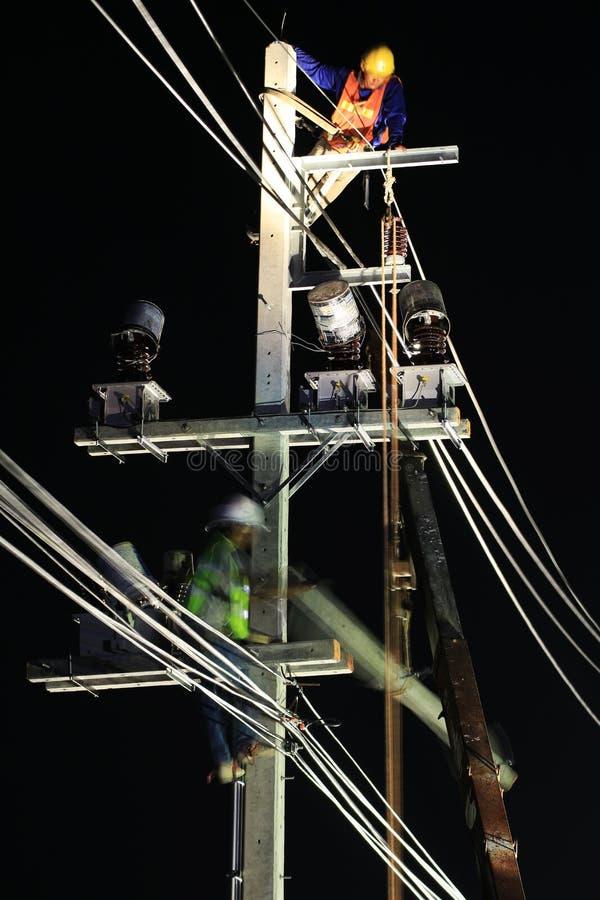 Techniciens travaillant à Polonais électrique la nuit images stock