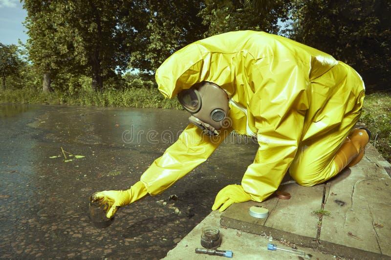 Technicus in chemisch beschermend kostuum die de steekproeven van de waterverontreiniging verzamelen stock foto's