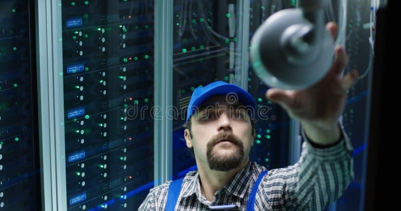 Technicus die camera controleren bij een datacentrum stock foto's