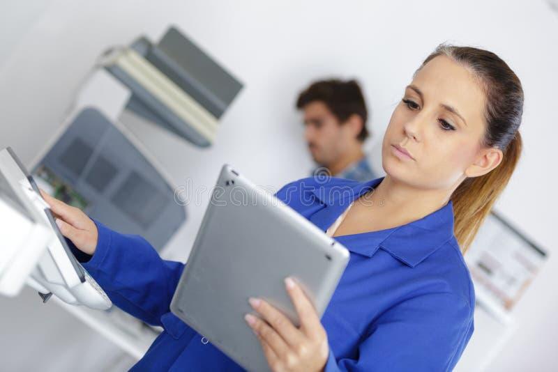 Technicus die digitale tablet houden terwijl het onderzoeken van fotokopieerapparaat royalty-vrije stock afbeeldingen
