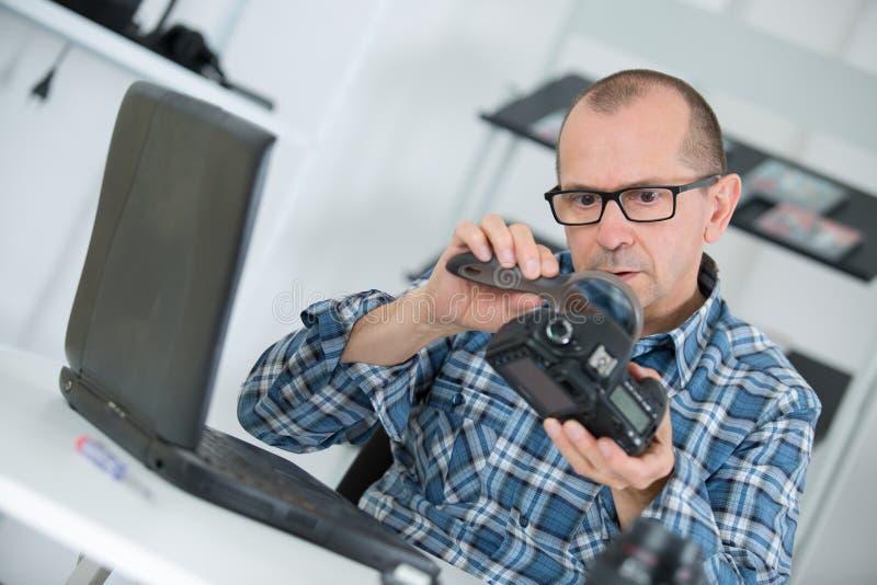 Technicus die en dslr camera onderzoeken herstellen stock afbeeldingen