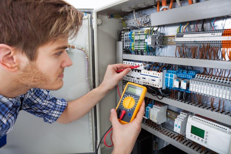 Technicus die fusebox met het meetapparaat van de isolatieweerstand onderzoeken royalty-vrije stock foto