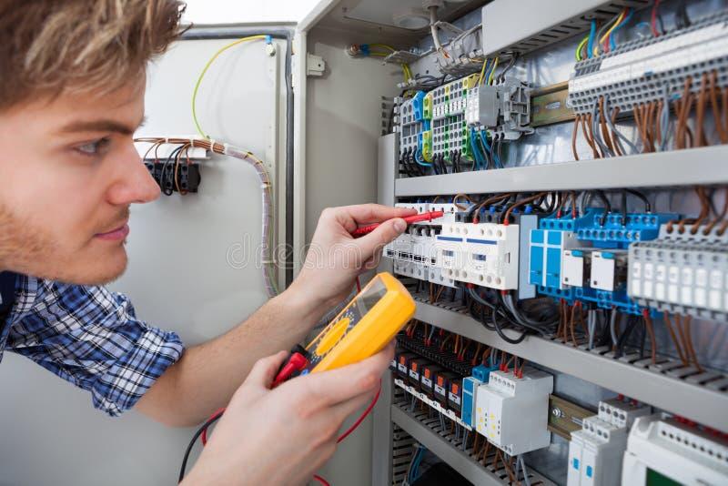 Technicus die fusebox met het meetapparaat van de isolatieweerstand onderzoeken stock afbeeldingen