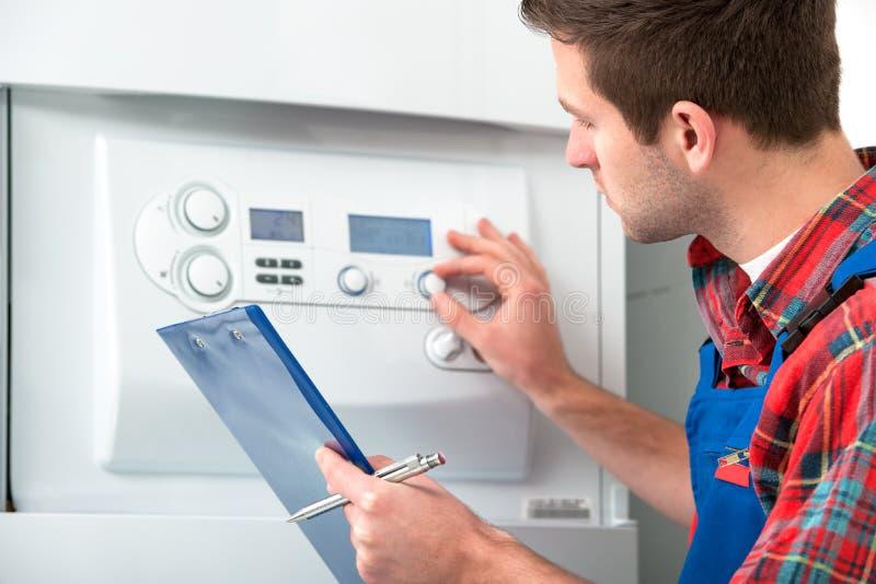 Technicus die het verwarmen boiler onderhouden stock afbeelding