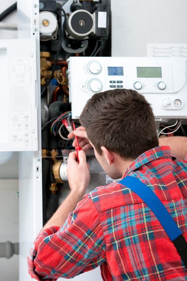 Technicus die het verwarmen boiler onderhouden stock foto's