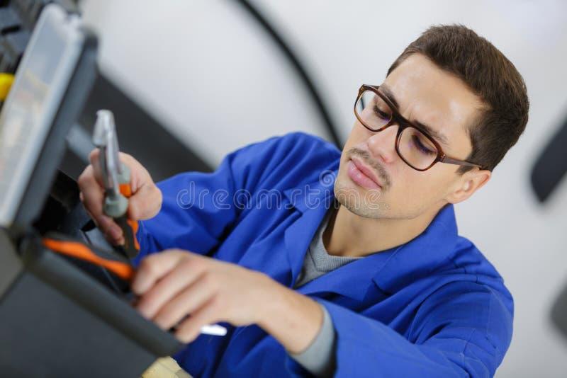 Technicus die hulpmiddel in toolbox zoeken stock foto's