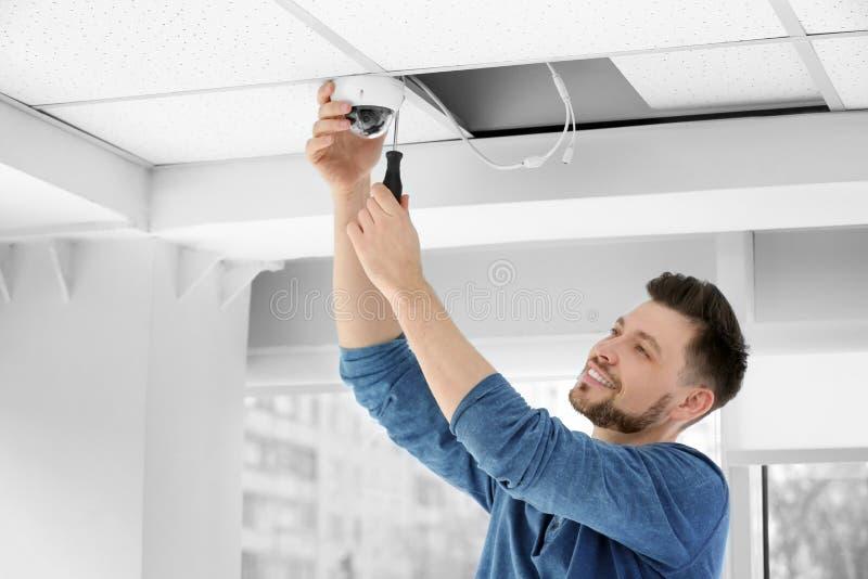 Technicus die kabeltelevisie-camera installeren stock afbeeldingen