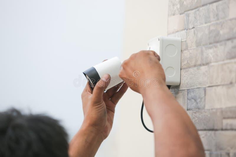 Technicus die kabeltelevisie-camera voor de veiligheidsdienst installeren stock afbeelding