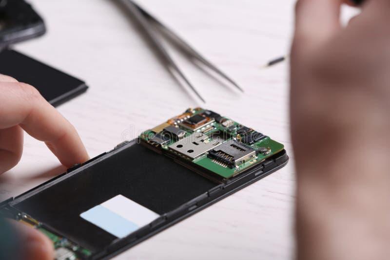 Technicus die mobiele telefoon bevestigen bij lijst De dienst van de apparatenreparatie stock afbeeldingen