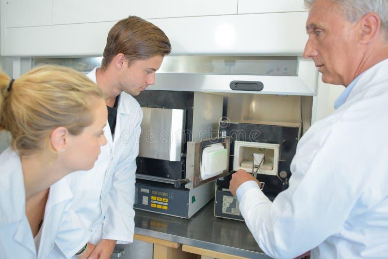 Technicus die product verwijderen uit machine met tang royalty-vrije stock foto