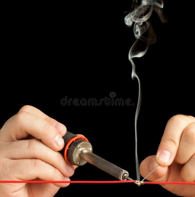 Technicus die twee draden met een soldeerselverbinding plakt. royalty-vrije stock fotografie