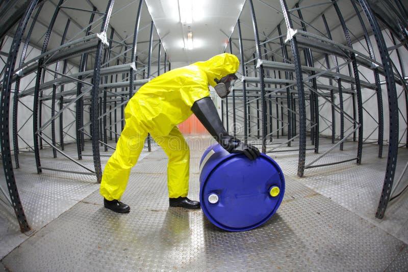 Technicus in gele eenvormig rollend het vat met giftige substantie stock fotografie