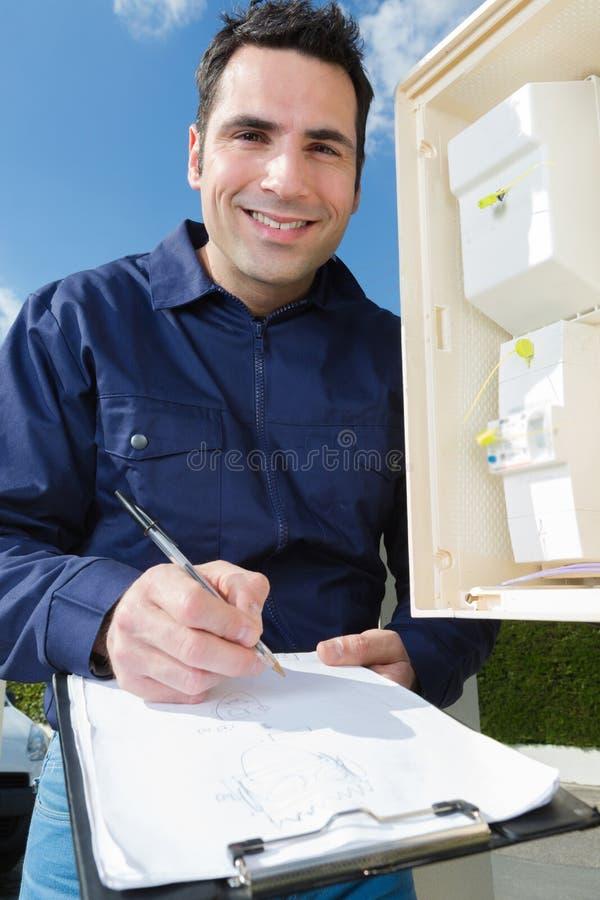 Technicus het schrijven de meter van de lezingselektriciteit op klembord stock afbeeldingen