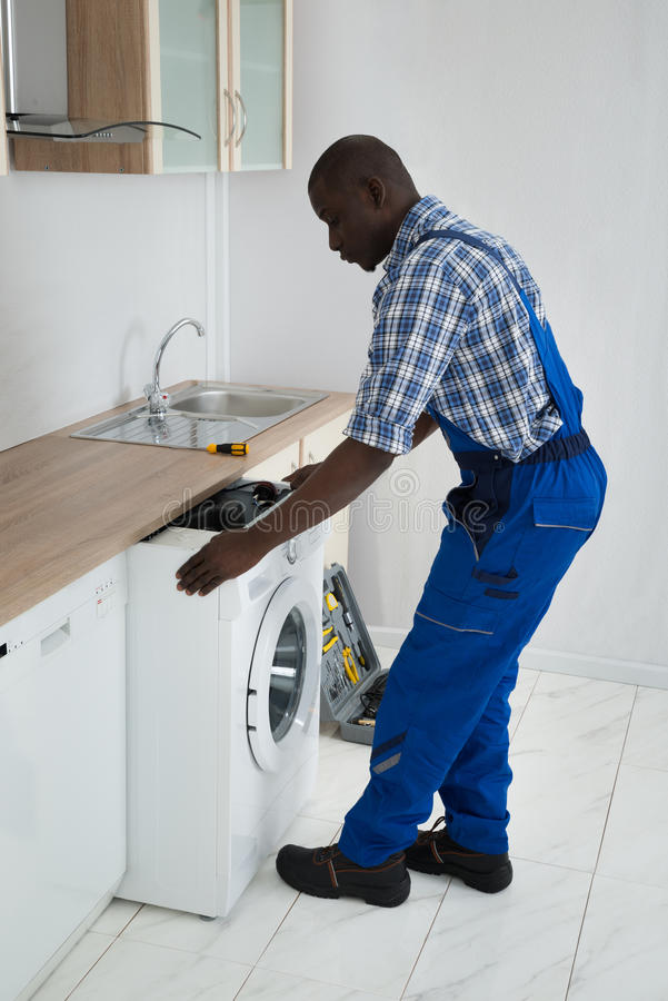 Technicus Pulling Washing Machine in Keuken royalty-vrije stock afbeelding