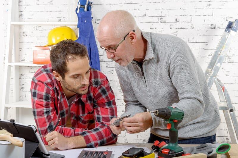 Technicus twee die mechanisch gedeelte onderzoeken stock foto's