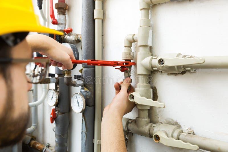 Technicusarbeider die onderhoudswerk voor het verwarmen doen syste stock afbeelding