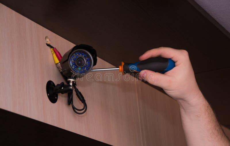 Technicusarbeider die videotoezichtcamera installeren Kabeltelevisie-cameraclose-up stock afbeelding