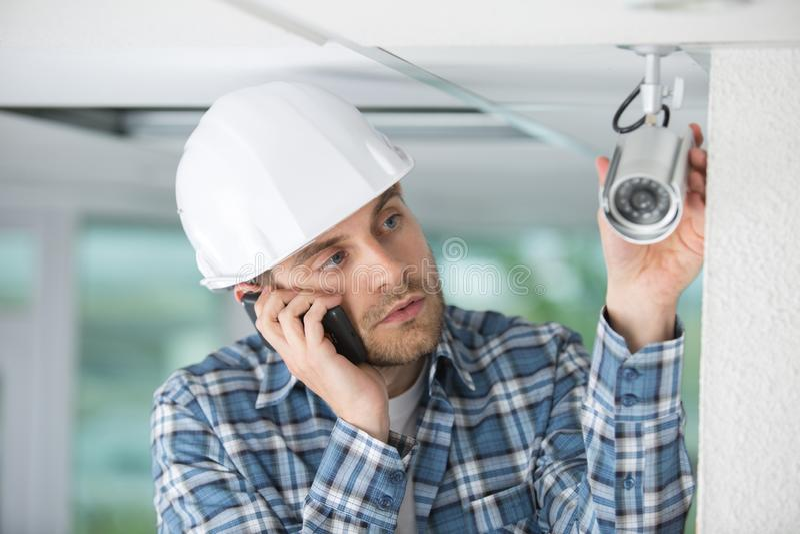 Technicusarbeider die videotoezichtcamera installeren op muur stock foto
