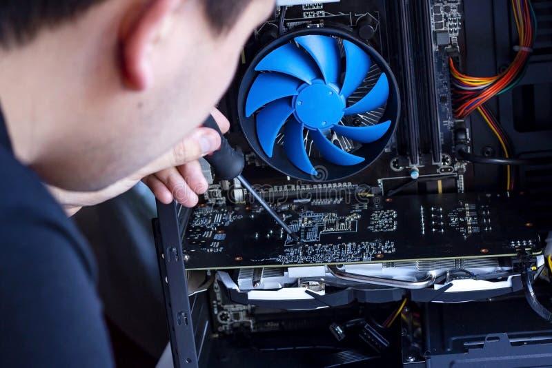 Technicusgreep de schroevedraaier voor het herstellen van de computer in zijn hand hardware, dienst, verbetering en technologie d stock foto's