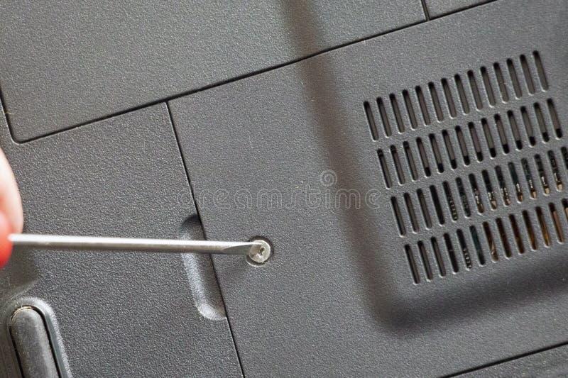 Technicusmens die schroevedraaier gebruiken om laptop computer te bevestigen of te bevorderen stock afbeeldingen