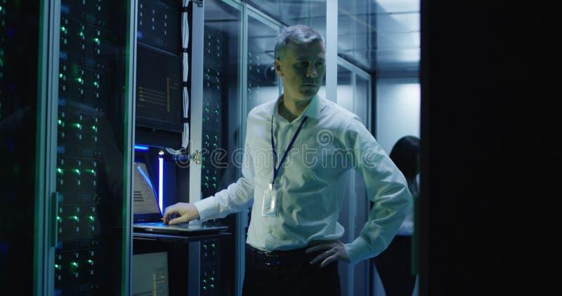 Technicy pracują na laptopie w centrum danych zdjęcia stock