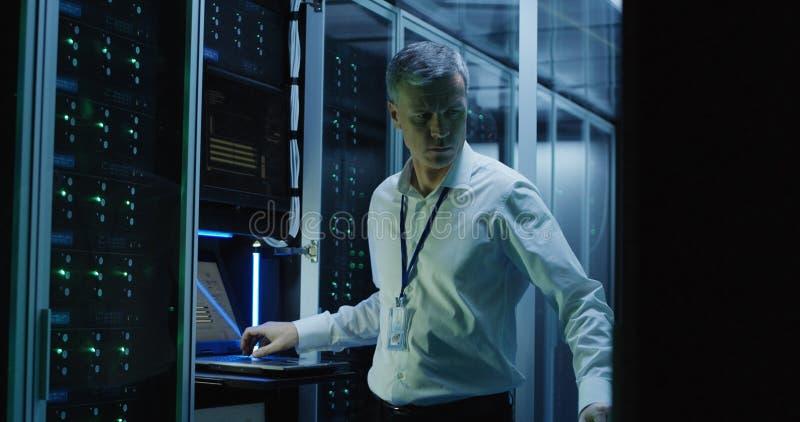 Technicy pracują na laptopie w centrum danych obraz royalty free