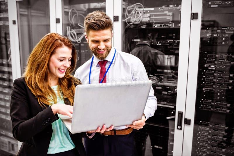 Technicy używa laptop podczas gdy analizujący serweru zdjęcie royalty free