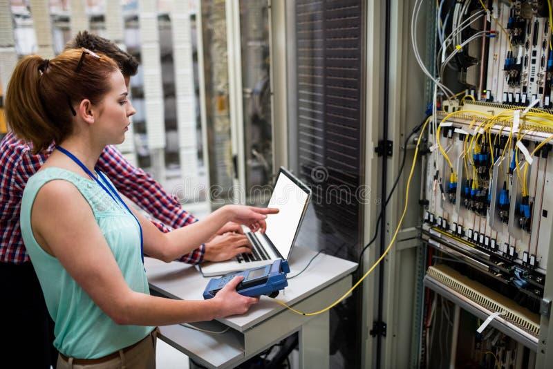Technicy używa laptop podczas gdy analizujący serweru zdjęcie stock