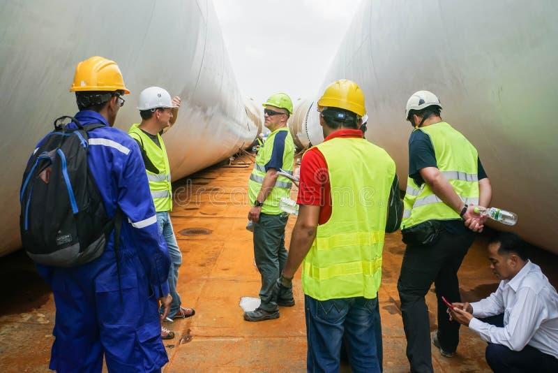 Techniczny inżynier w mechanika kombinezonie z zbawczym hełmem pod dyskusją na pokładzie naczynia w Bangkok zdjęcie royalty free