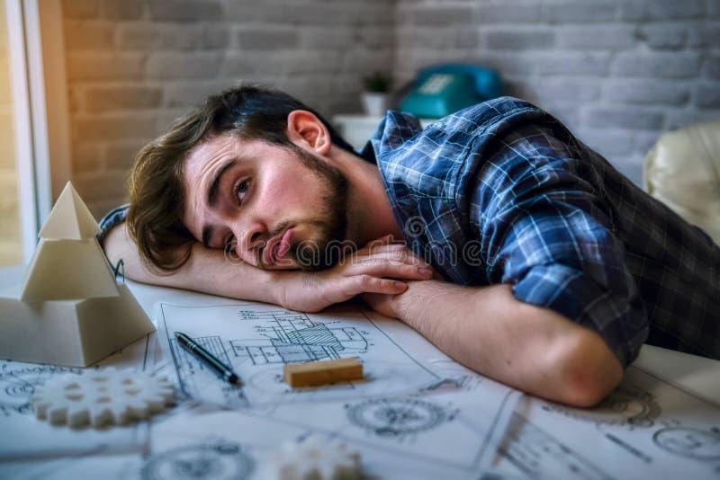 Techniek de mens die werkt zich en slaap op het bureau met blauwdrukmechanische gedeelten in bureau werken over het hebben van ee stock fotografie