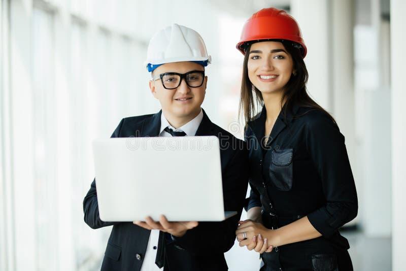 Techniek en architectuurconcept Ingenieurs die aan een bouwterrein werken die laptop, architectenmens houden die met ingenieur w  royalty-vrije stock foto