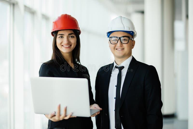 Techniek en architectuurconcept Ingenieurs die aan een bouwterrein werken die laptop, architectenmens houden die met ingenieur w  stock fotografie