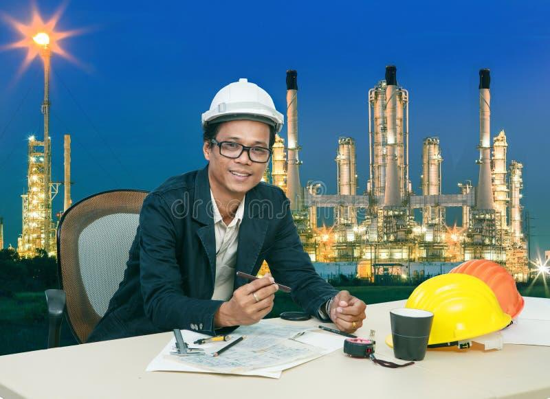 Techniekmens die aan lijst tegen mooie verlichting van de installatie van de olieraffinaderij werken stock foto's