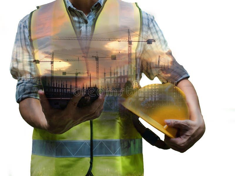 Techniekmens die zich met gele veiligheidshelm bevinden die en tablet houden op witte achtergrond, het werkconcept wordt geïsolee stock foto's