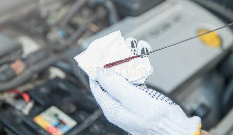 Technik sprawdza nafcianego poziom w samochodowym silniku zdjęcie royalty free