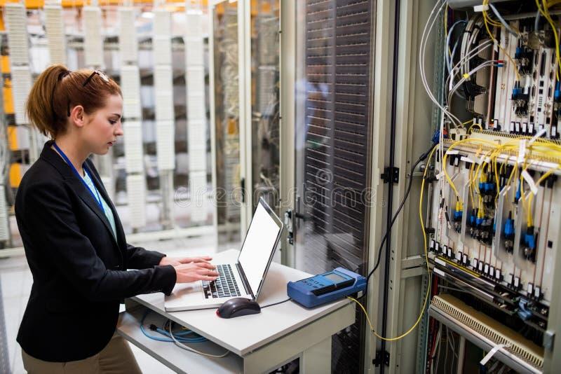 Technik używa laptop podczas gdy analizujący serweru zdjęcie stock