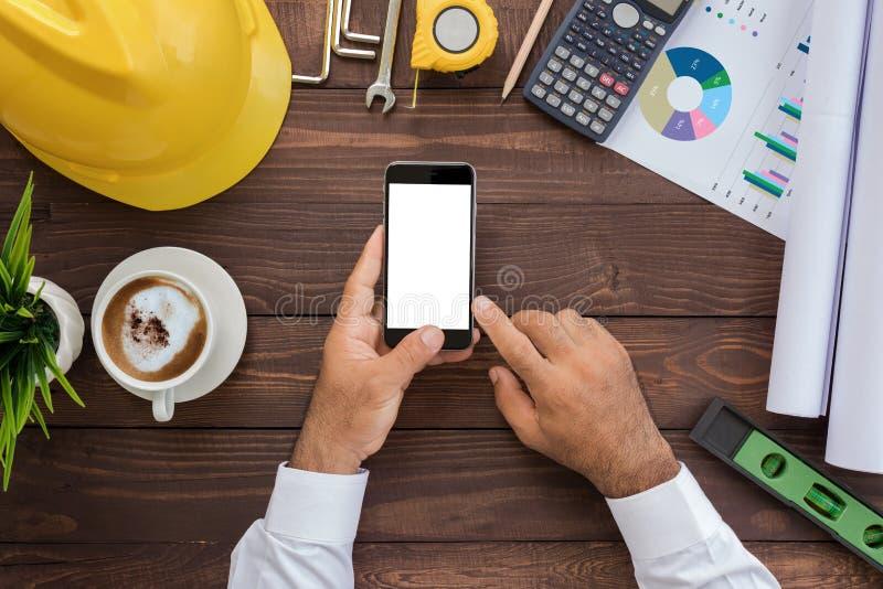 Technik unter Verwendung des Telefons auf seiner Draufsicht des Arbeitsplatzes lizenzfreies stockbild